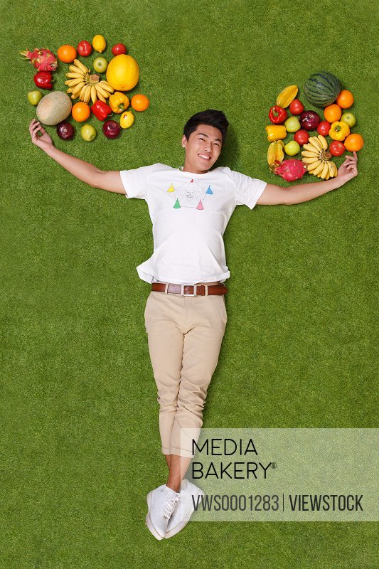 Young man lying on grass with fruits
