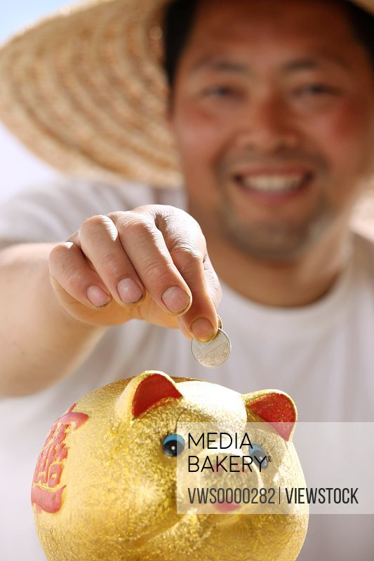 Farmer putting coin in piggy bank