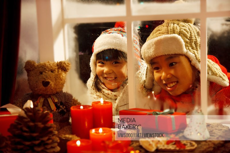 Girl and boy looking at Christmas gift through window