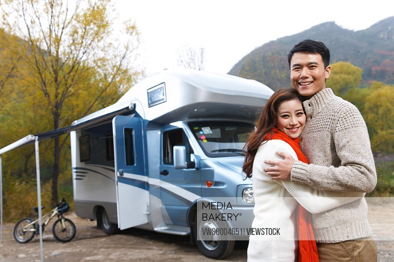Embracing couple beside a motor home