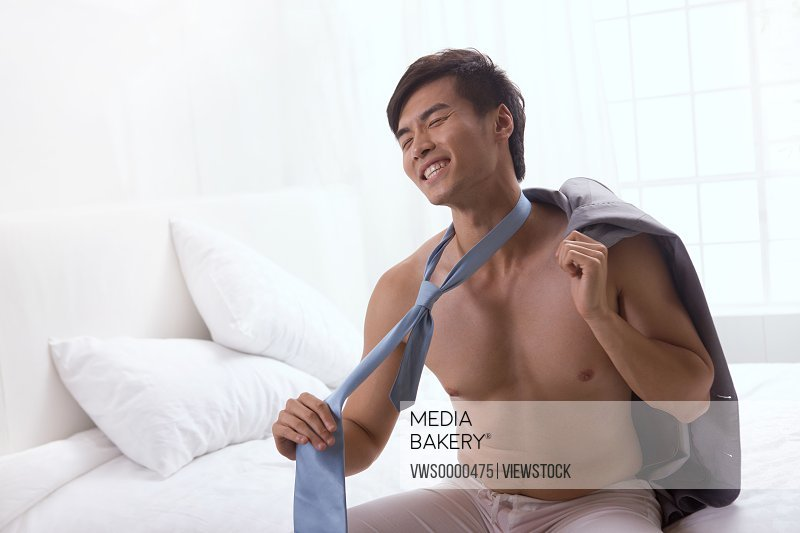 Young man sitting on bed taking off cloth
