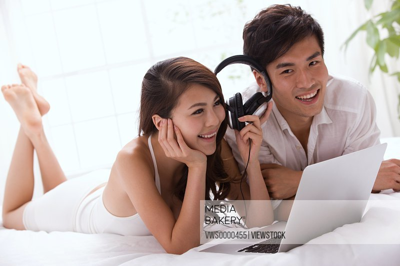 Young couple using laptop and listening to music on bed