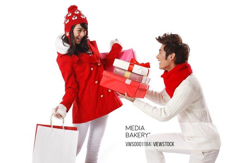 Young couple holding Christmas gift