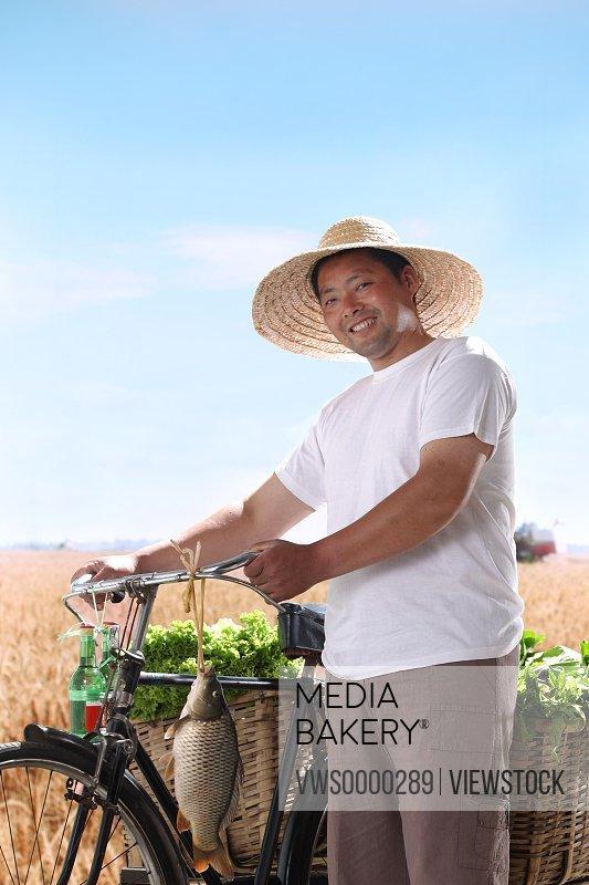 Farmer walking bike with vegetable