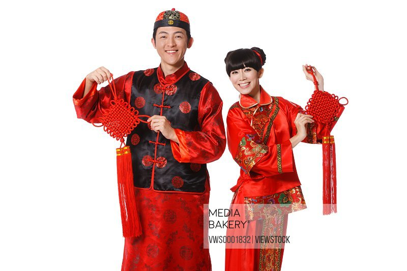 Young couple dressed in Chinese traditional clothes holding Chinese knot