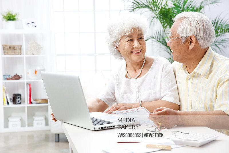 Old couple use a computer