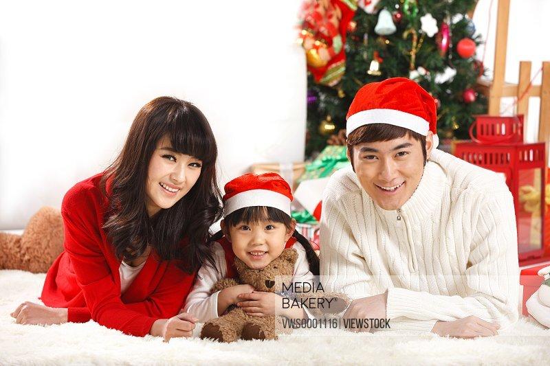 Family wearing Christmas hat lying on floor