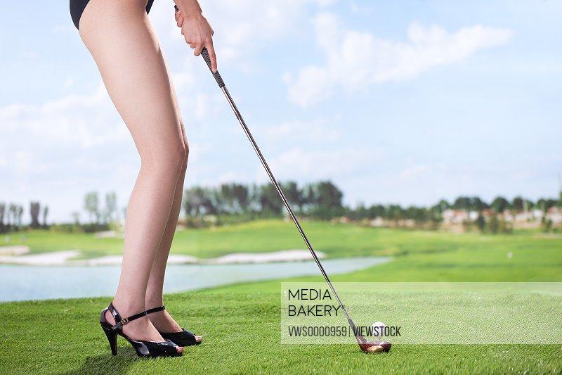 Sexy woman playing golf