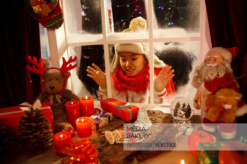 Boy looking at Christmas gift through window