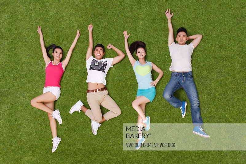 Young people lying on grass