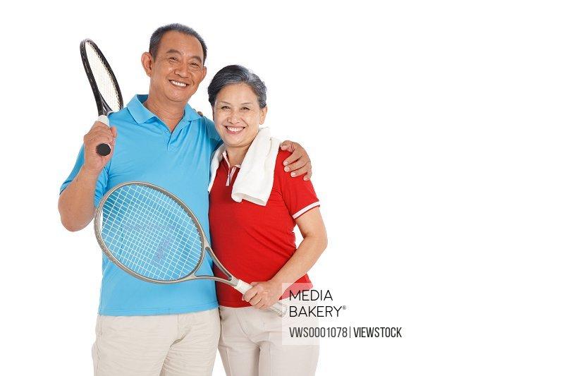 Old couple holding racket