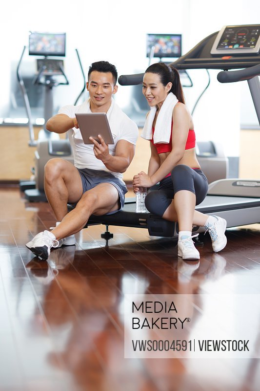 Young man and woman in fitness gym