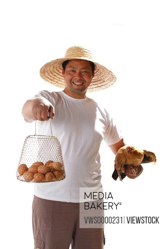 Farmer holding eggs and chicken