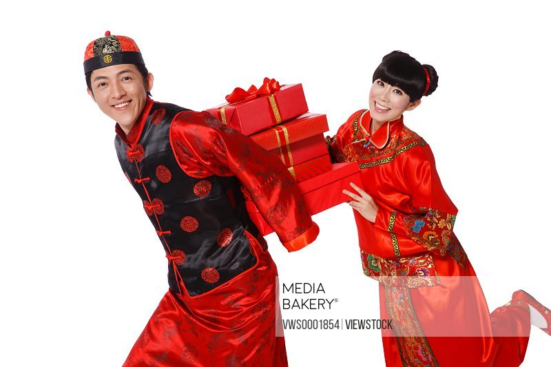 Young couple dressed in traditional clothes celebrating Chinese New Year