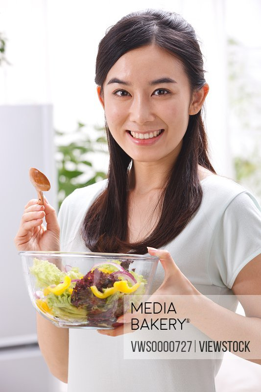 Young woman holding vegetables in kitchen