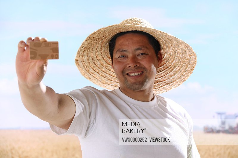 Farmer holding credit card in field