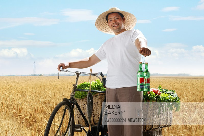 Farmer in wheat field with bicycle and vegetables