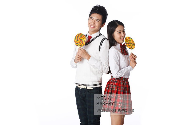 Student boy and girl with lollipop