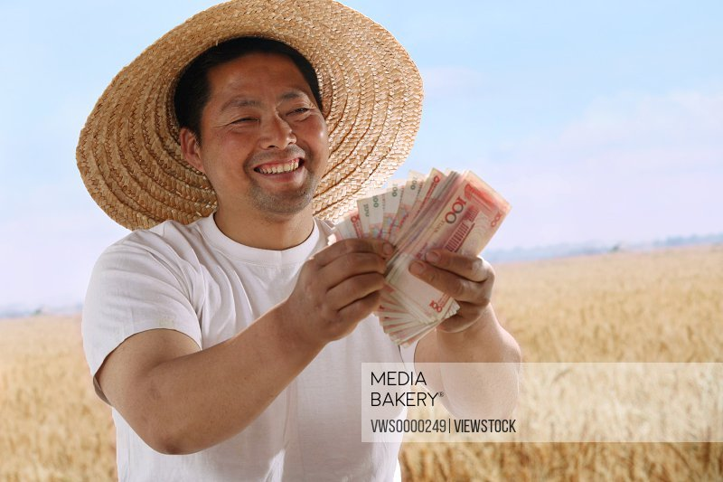 Farmer counting money in field