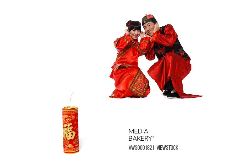Young couple in traditional clothes with fire cracker