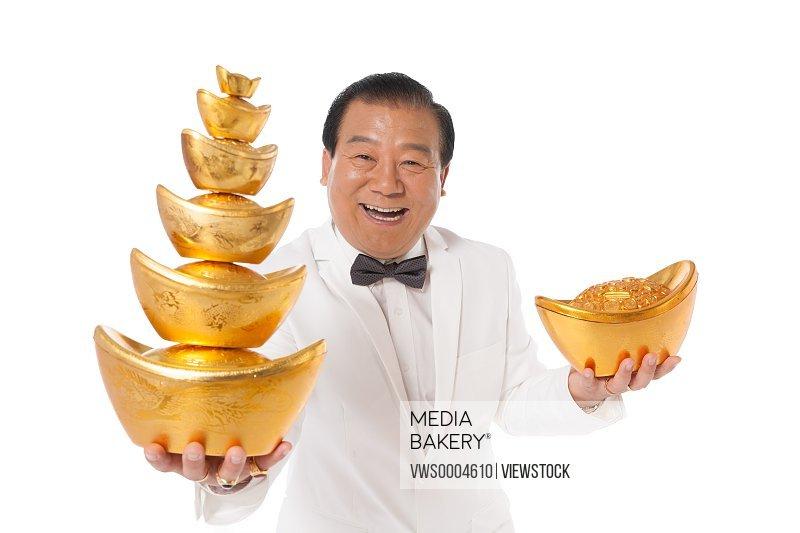 Successful man holding a gold ingot