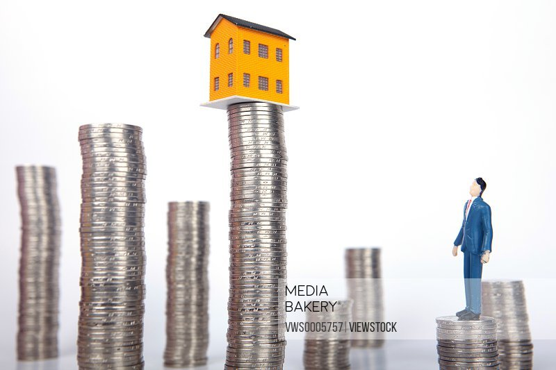 Businessman standing on stack of coins