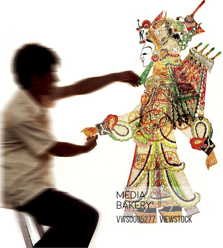 man playing Chinese shadow puppet on white background