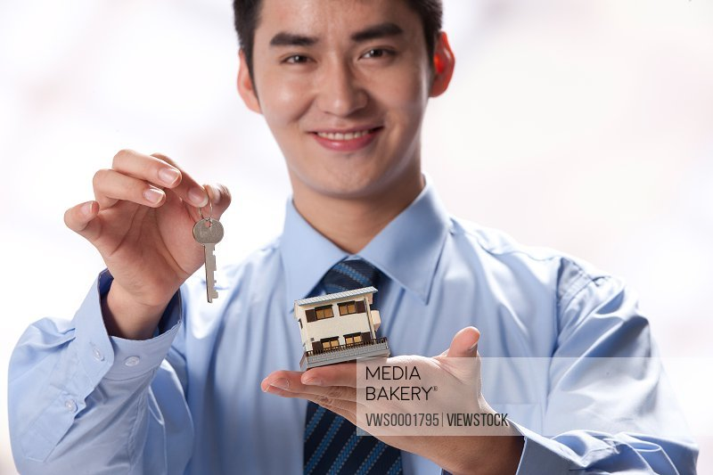 Young businessman holding key and artificial house