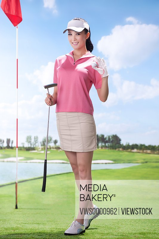 Young woman holding golf clubs