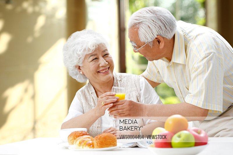 Happy elderly couple holding juice