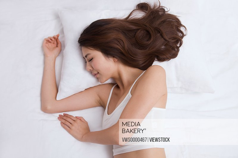 Young lady sleeping on bed
