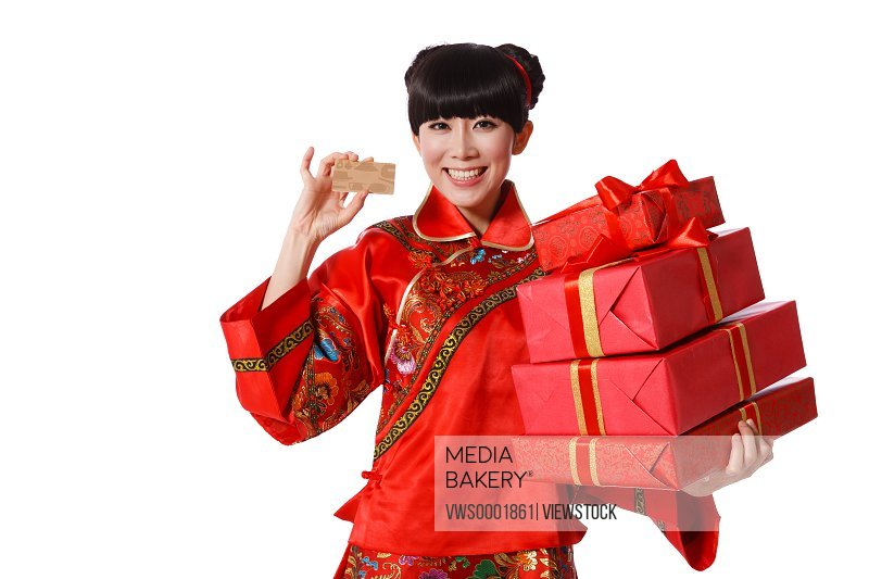Young woman dressed in Chinese traditional clothes holding two wrapped boxes on Chinese New Year