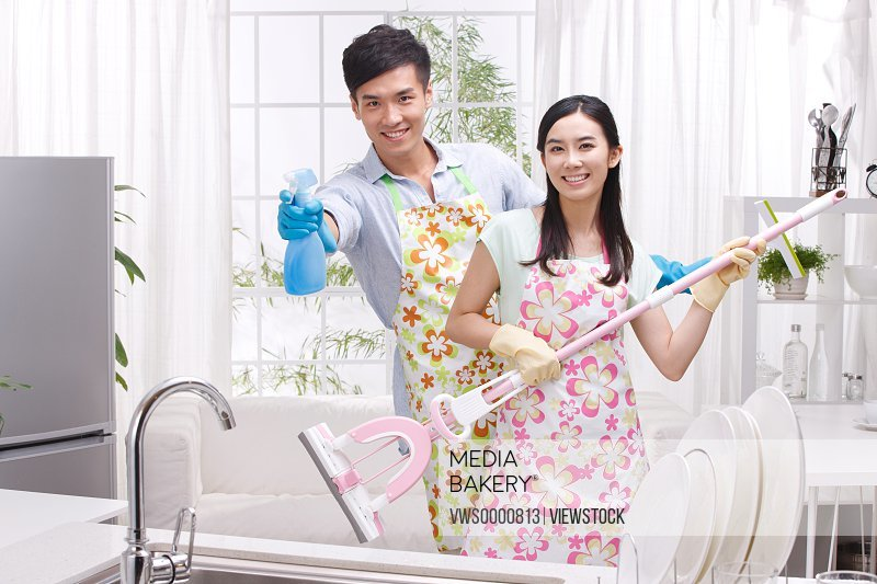 Young couple cleaning room