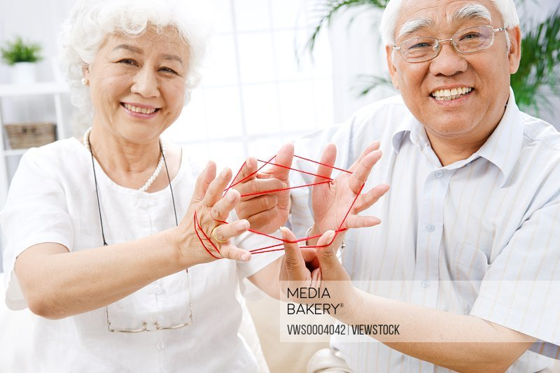 Old couple play Cat's cradle