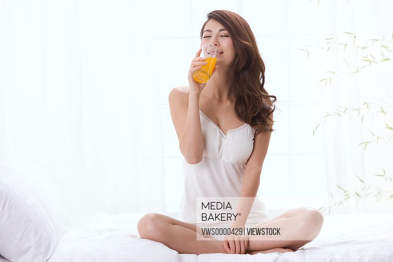 Young lady drinking juice on bed