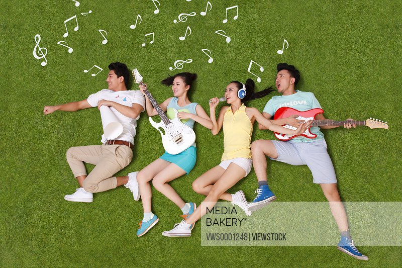 Young people on grass playing musical instruments