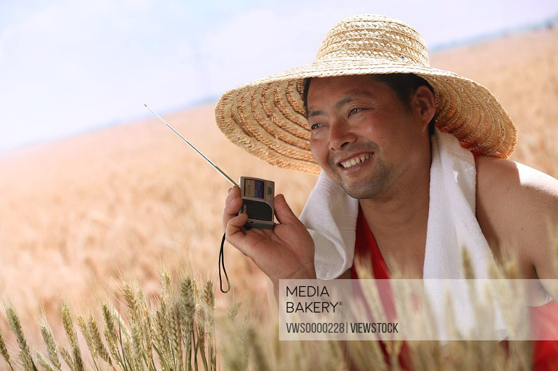 Farmer listening to radio in wheat field