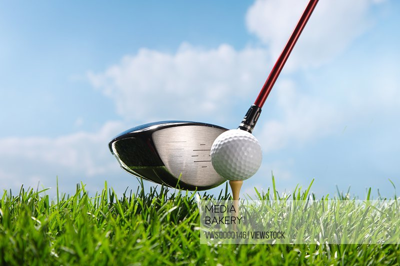 Golf club teeing up to hit ball