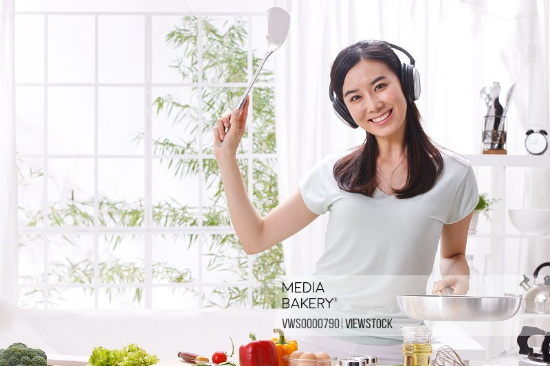 Young woman listening to music and cooking in kitchen