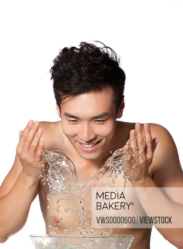 Young man washing face