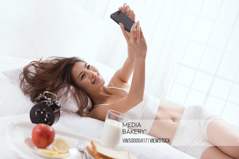 Young lady looking at mobile phone on bed