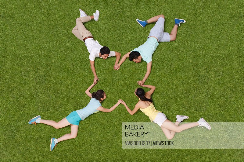 Young people lying on grass hand in hand