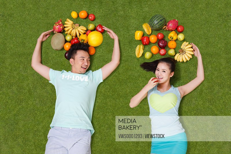 Young couple lying on grass with fruits