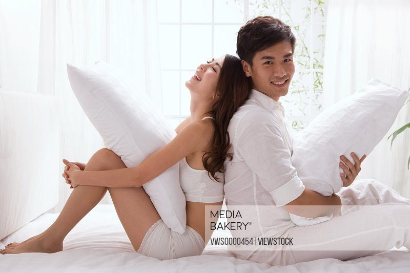 Young couple sitting on bed back to back