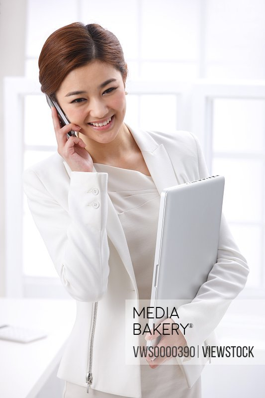Young business lady making phone call and holding laptop
