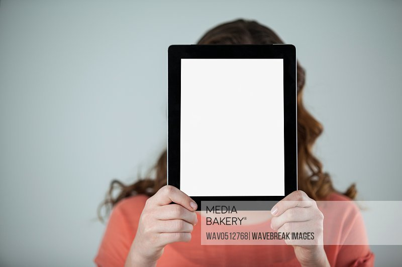Woman holding a digital tablet in front of her face