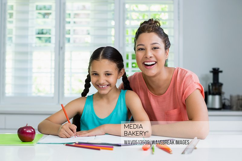Mother assisting her daughter in doing her homework at home