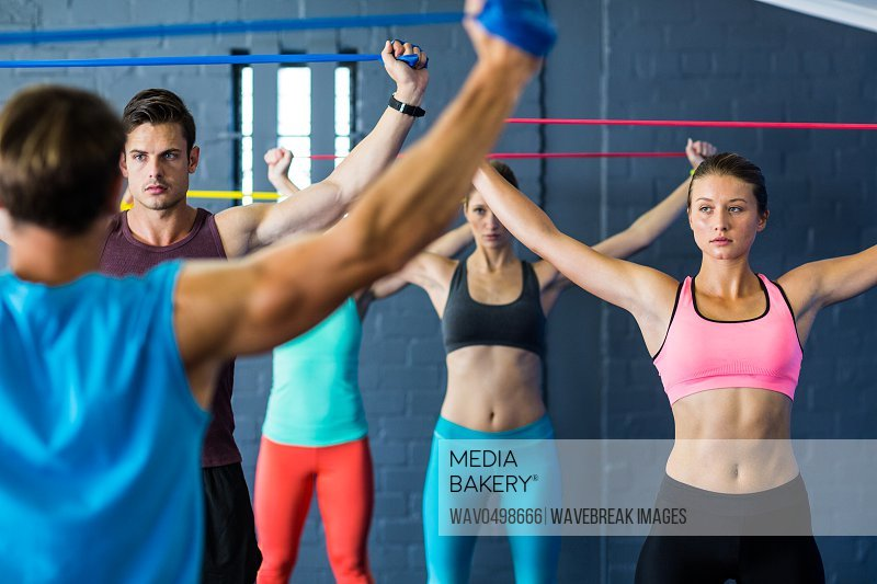 Athletes looking at instructor while exercising with resistance band