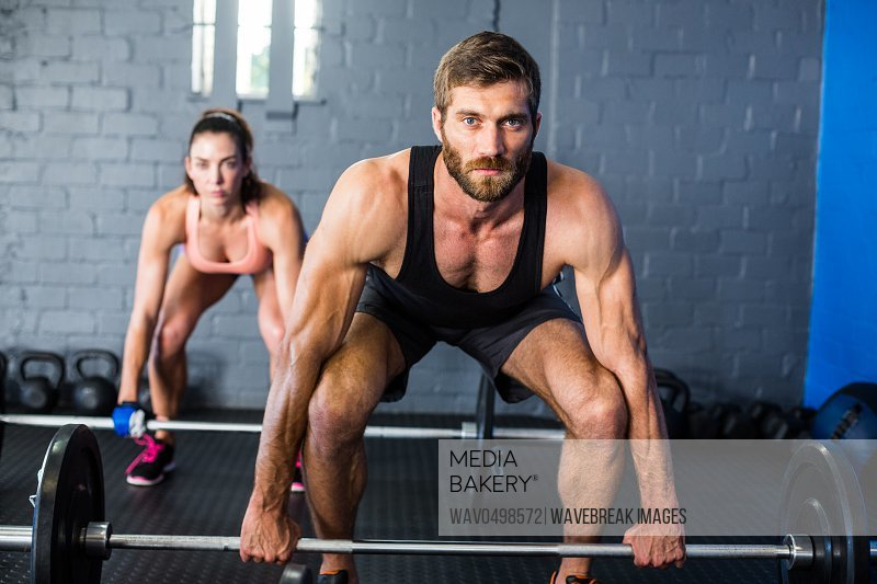 Portrait of athletes lifting barbell in gym