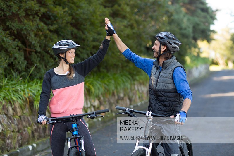 Happy biker couple giving high five while riding bicycle on the road